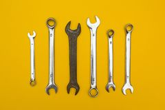 Old wrench on a background of new. yellow background royalty free stock images