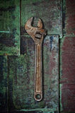 Old wrench on rusty surface. Royalty Free Stock Photography