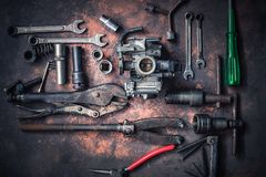 Old wrench and tools and carburetor on rusty background . moto. Rcycle tools and maintenance equipment and repair stock image