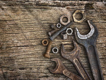 Old wrenches on the nuts and bolts on a wooden grungy background Stock Photos
