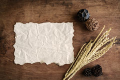 Old wrinkld paper on old wood background with dried flower Royalty Free Stock Images