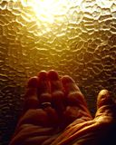 Old wrinkled aged hand praying toward the light from window stock photo