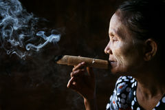 Old wrinkled Asian woman smoking Royalty Free Stock Photos