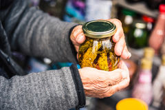 Old wrinkled hands hold a jar with mountain jam from the leaves of Caucasian trees Royalty Free Stock Photos