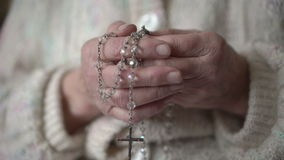 Old wrinkled hands holding rosary and praying with icon stock video