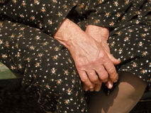 Old wrinkled hands on woman. Grandmothers wrinkled old hands and old dress Royalty Free Stock Image
