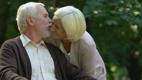 Old wrinkled man and woman kissing with tenderness in park, happiness and love