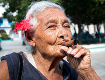 Old wrinkled woman with red flower smoking cigar Royalty Free Stock Photos