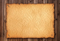 Old  wrinkly paper on brown aged wood. Old paper sheet. Digital Stock Image