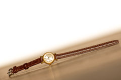 Old wristwatch with scratches on glass and leather strap. On wooden background Royalty Free Stock Image