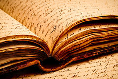 Old Writings. Close-up of script writing on pages inside an old open book resting on more pages Stock Photos