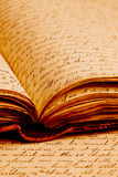 Old Writings. Close-up of script writing on pages inside an old open book resting on more pages Stock Image