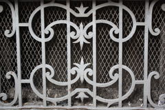 Old wrought iron fantasy shaped and net frame. Old wrought iron skylight fantasy shaped frame of a window near sidewalk with iron net Stock Photo