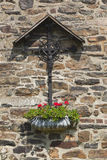 Handicraft wrought iron cross against old stone facade of Farm in Belgium Stock Photo