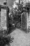 Old wrought iron full size garden gate and brick wall in black a Stock Photo