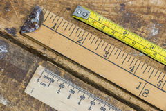 Old yard stick, ruler and tape measure on scratched workshop tab Stock Image
