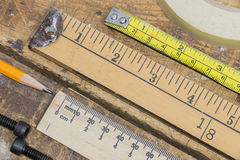 Old yard stick, rulers and tape measures on workshop table with Stock Photography