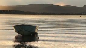 old yawl boat floating at sunset on the lake Stock Image