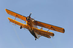 Old yellow airplane flying high in the sky.  Royalty Free Stock Photography