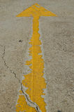 Old yellow arrow on the road Royalty Free Stock Photo