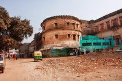 Old yellow auto rickshaw drive past the walls of Ramnagar Fort in Varanasi Royalty Free Stock Photos