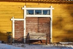 Old yellow barn with brown door royalty free stock photo
