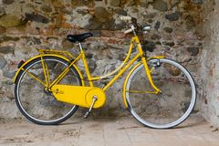 Old yellow bike. On the wall royalty free stock images