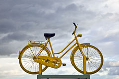 Old yellow bike on a roof as hint for a bike ferry in dark cloud Stock Photo