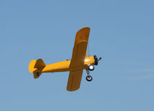 Old yellow biplane in flight Royalty Free Stock Photo