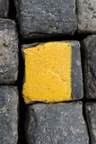 Old yellow and black granite road cubes or cobbles as background or wallpaper. Vertical image. Old yellow and black granite road cubes as background or royalty free stock photos