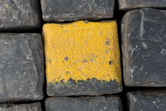 Old yellow and black granite road cubes or cobbles as background or wallpaper. Vertical image. Old yellow and black granite road cubes as background or stock photography