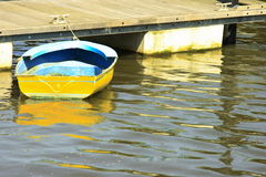 Old Yellow Boat at the Dock. An old yellow boat tied up to the wooden dock Royalty Free Stock Photography