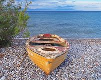 Old yellow boat on Nikolaiika Beach and the Corinthian Gulf, Greece. An old yellow boat sits on Nikolaika Beach near the blue waters of the Corinthian Gulf on Stock Photography