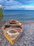 Old yellow boat on Nikolaiika Beach and the Corinthian Gulf, Greece. An old yellow boat sits on Nikolaika Beach near the blue waters of the Corinthian Gulf on Stock Images