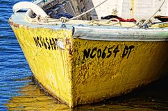 Old Yellow Boat in OBX. An old yellow boat tied to a pier on the coast of North Carolina stock photos