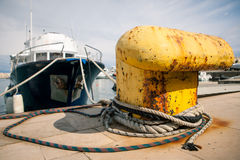 Old yellow bollard in the port Stock Photos