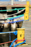 Old yellow bollard with rope in marina Stock Images
