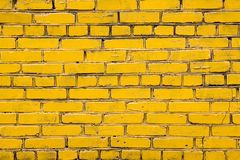Yellow brick wall with dark joints stock images
