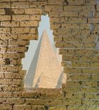 Old yellow brick wall in ruins with a big opening in it viewing on some egyptian pyramids. A Old yellow brick wall in ruins with a big opening in it viewing on stock photos