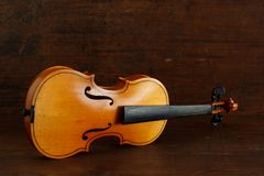 Old yellow broken violin without strings lies on a side on brown antique wood background stock photos