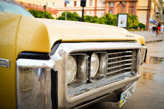 Old yellow Buick after rain. Odessa, Ukraine - July 15, 2015. Old yellow Buick after rain Stock Image