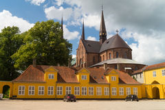 Old yellow building in front of Roskilde Cathedral. Roskilde Cathedral Domkirke in Denmark  is the burial site for the Royal Family. Since 1995 it has been Stock Photos