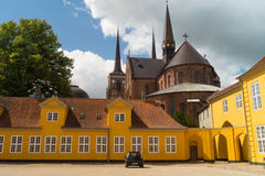 Old yellow building in front of Roskilde Cathedral. Roskilde Cathedral Domkirke in Denmark  is the burial site for the Royal Family. Since 1995 it has been Stock Photography