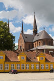 Old yellow building in front of Roskilde Cathedral Stock Image