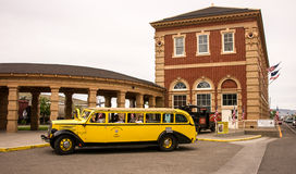 The Old Yellow Bus. Livingston, MT, USA, June 29, 2015: Tourists board a vintage historic yellow bus for a chartered excursion from the Livington Montana traind stock images