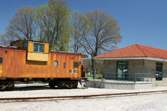 Old yellow caboose. An old yellow caboose next to an abandoned depot beside railroad tracks Royalty Free Stock Photo