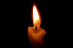 Old yellow candle on black. Old yellow candle on black background Stock Images