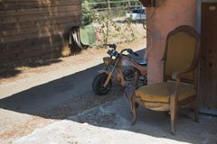 The old yellow childrens motorcycle. The old broken brown and yellow chair is standing behind the wall near the old yellow childrens motorcycle Royalty Free Stock Photos