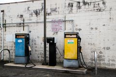 Old yellow diesel pump and old blue gasoline pump in front of old white brick wall stock image