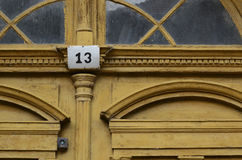 Old yellow door with 13. Stock Photo